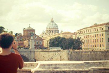 Turista sul ponte Sant'Angelo di Roma fotografa San Pietro